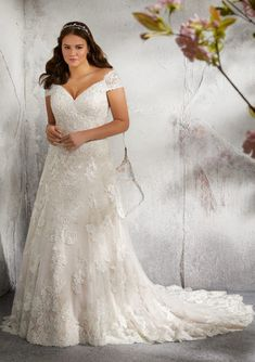 Shop Morilee's Lilith Wedding Dress.  This stunning cap sleeve Lilith wedding dress features extraordinary appliquès, embroidery, crystals, and beading on an intricately designed net gown. Available in white, ivory, and ivory/rosé, this v-neck neckline completes this a-line silhouette.