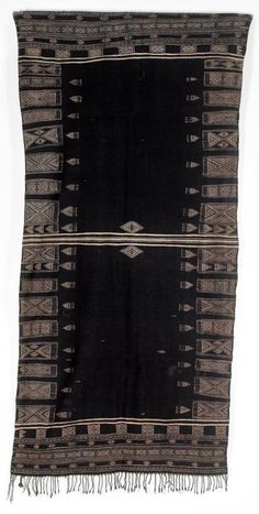 Africa | A shawl, Bakhnuq, from Tunisia | Wool and cotton; the black ground divided in the centre by a single stripe flanked by a lozenge motif, with finely woven mushroom brown borders of geometric panels and bands, fringes to either end