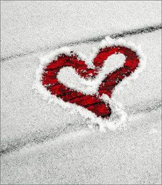 Heart traced in snow on red object.