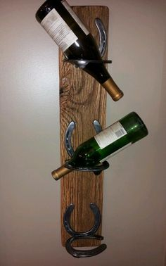 Rustic wine rack. made with horse shoes attached to old barn wood. Stores 3 bottles cork down.