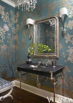 In Nashville, designer Suzanne Kasler created this powder room with shimmering Gracie wallpaper, vanity and fittings from Waterworks, sconces by Circa Lighting and a stool by David Iatesta.