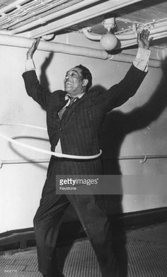 1958: American big band leader and legendary jazz pianist Duke Ellington (1899 - 1974), composer of between 2000 / 5000 tunes, shows how he can hula-hoop on the deck of SS Ille de France before embarking at Plymouth.