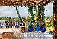 Sobre a laje da garagem, o terraço com cobertura de bambu e estrutura de toras de eucalipito, nas quais cresce a trepadeira tumbérgia