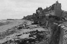 D-Day in Normandy. Note the plane on the beach that may have had a water landing, then rolled in on the high tide against the sea wall.