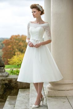 Tea length a-line wedding dress features strapless sweetheart underskirt in bateau neckline sheer lace overlay,  half sleeves, matching with sash.