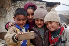 Syrian children who fled their homes due to the Assad regime forces' attacks on civilians take a selfie at a makeshift tent camp in Eastern Ghouta, Damascus, on April 19.