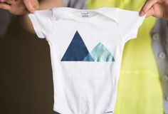Oh baby! Use fabric paint and stencils to take a plain white onesie from awww! to awesome! Simple triangle shapes form a mini mountain