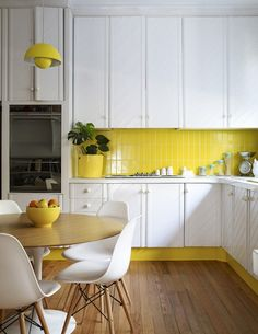 This bright yellow tile pops against the sleek white cabinets.