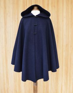 $144.50 Womens hooded cape made from boiled wool fabric in a rich navy blue color . Fastened with three toggle buttons, this cape Designed and handmade in Scotland.More versatile
