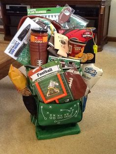 Tailgating basket for an auction item. There is plates, cups, napkins, snacks, salt and pepper shaker, cutting board, tablecloth, etc all packed into a rolling cooler! It did well...it cost a little over $50 to make and went for $65 at auction. This was a fun basket to put together, but it was hard to keep it from falling forward! Camping Gift Baskets, Football Gift Baskets, Raffle Gift Basket Ideas, Raffle Baskets, Raffle Ideas, Theme Baskets, Themed Gift Baskets, Auction Projects, Auction Ideas