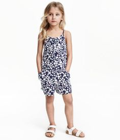 Jumpsuit in cotton jersey with a printed pattern. Narrow shoulder straps, elasticized waist with decorative bow at front, side pockets, and short legs.