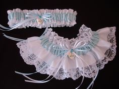 """An exquisite and elegant wedding garter set. The keepsake garter in White lace is overlayed with white and light blue satin. Both garters are decorated with accent bows, silver """"Love"""" charm, and light blue rhinestone."""