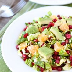 Chopped brussels sprouts with avocado, pomegranate arils, oranges, and a citrus dressing