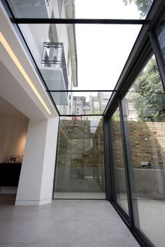 The versatile glass extension on this traditional home uses a glass roof & frameless structural glass sides which connect to our minimally framed sliding doors...