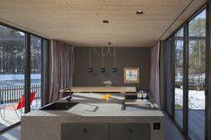 Offene Küche mit bodentiefen Fenstern in schickem Holzhaus