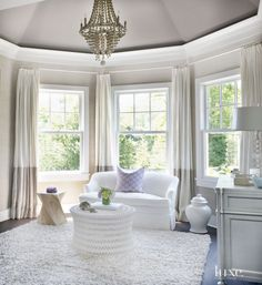 Color-blocked drapes, a reupholstered vintage loveseat and a textured West Elm rug imbue the sitting area in the master bedroom with comfort and style. The round textured accent table is from Oly and the chandelier is from HB Home.