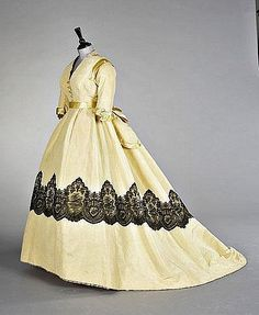 A pale yellow ottoman velvet evening gown, circa 1865, the bodice with yellow satin trimming and buttons, matching waistband with large bow, the trained skirt applied with broad band of black Chantilly lace, (3