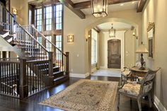 Arched foyer entry to home with stairs and large area rug