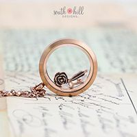 """MAY LOCKET OF THE MONTH """"Give your heart and soul to me and life will always be la vie en rose…gold.""""  Our Large Rose Gold Locket is filled with a Vintage Rose, Key, and Feather—all in Rose Gold—and topped with two shimmering Crystals."""