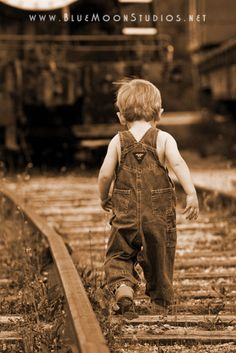 Working on the railroad. Boy in overalls playing on inactive railroad tracks.