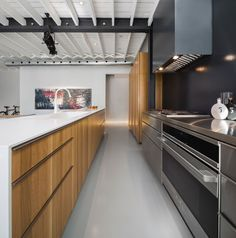 White corian countertops, stainless steel appliances, and a large storage cabinet.