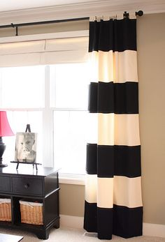 """This blog shows how to make these striped curtains using off white drapes (I would choose some that aren't tab top), 14"""" strips of black fabric, adhere with fabric webbing and ribbon on raw edges. Awesome~ Want to make these for our Game Room!"""