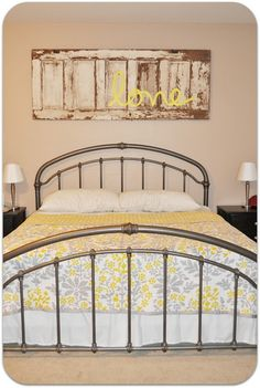 An old door as decor above the bed with a simple word on it. It would make a great headboard idea w a darker wall