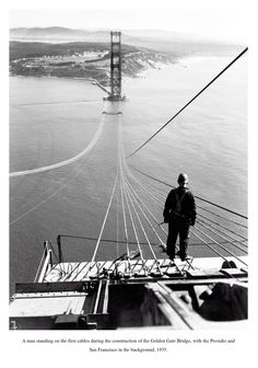 Ein Mann steht 1935 auf den ersten Seilen der Golden Gate Bridge mit der Presidio und San Francisco im Hintergrund.