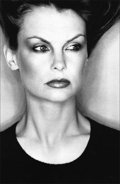 Jean Shrimpton by David Bailey, 1974. The facial expression is quite stern and challenging in this image, and appears to be either lost in thought or looking at a person. Even though there isn't direct eye contact, there is still an atmosphere that she is superior because of this.