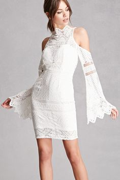 A knit crochet overlay dress by Selfie Leslie™ featuring shoulder cutouts, a high neckline, scalloped trim, a padded bust, a buttoned cutout back, concealed back zipper, and long bell sleeves.