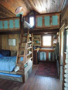 """Ladder in middle of room incorporating a storage or bookcase """"room divider"""". Great idea, especially if the sides are too low to fit the staircase off to the side."""