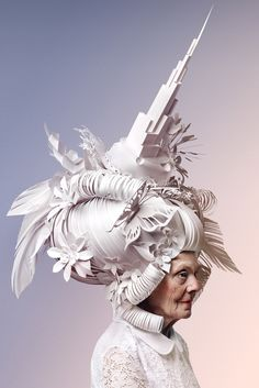 Paper artist Asya Kozina was inspired by the decadent wigs found in Baroque and Rococo still lifes, tall masses of hair adorned with objects that represent the ideals of luxury and beauty in the 17th and 18th centuries. Her series Skyscraper on the Head imagines how these outdated accessories might