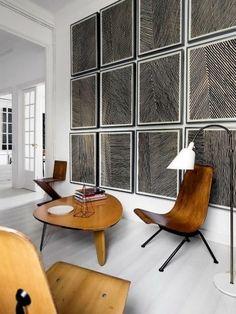 salon moderne de luxe avec des fauteuils en bois au design sophistiqué, murs avec des panneaux carrés en noir et blanc, parquet blanc, table en bois claire avec forme ronde irrégulière, luminaire sur pied avec abat jour blanc