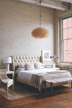 soft.... hardwood floors are perfectly aged/hued, light fixture is sculptural, textural, white painted brick, tufted headboard, bench adds another layer of texture, simply perfect....