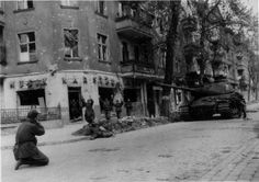 Germans surrender in the streets of unidentified city. Heavy Russian tank keeps an eye, just in case.