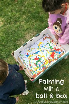 Kids painting together using a ball and a box