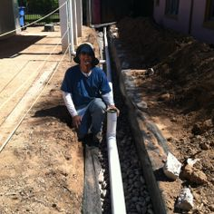 Chip posing with the level perforated pipe in the French drain.