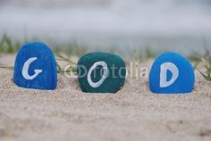 In God we trust. Colourful stones composition on the sand