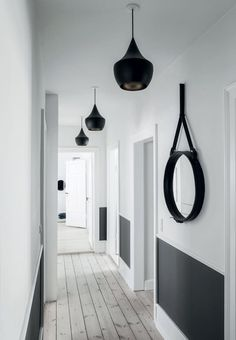 Bright and minimalistic entryway with tall panels, hardwood flooring and pendants designed by Tom Dixon.