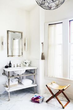 Chic bathroom with marble floors, large chandelier, and a folding chair