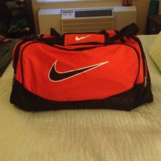 Nike Duffel Bright orange Nike duffel, medium size. In awesome condition, only flaw is where I've marked out my name where it was written on the inner handle (picture #4). Nike Bags Travel Bags