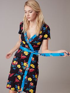 Rendered in vibrant, graphic prints, this 100% silk dress falls just above the knee and features the classic wrap style closure and construction, short sleeves, a V-neck, and a band along the waist to enhance a feminine silhouette.