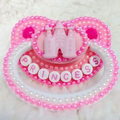 Pearl Princess Adult Pacifier For the princess that loves being covered in pearls this pacifier features a pink castle with matching pearl scheme. Give your little princess the pacifier they deserve!