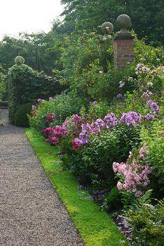 Grass edging, flower garden, ivy on stone wall