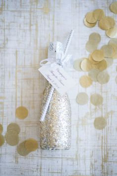 Glitter-adorned miniature Champagne bottles can work double-time as place cards for assigned seating or as bright party favors that guests can bring home.  See more at Fab You Bliss.   - CountryLiving.com