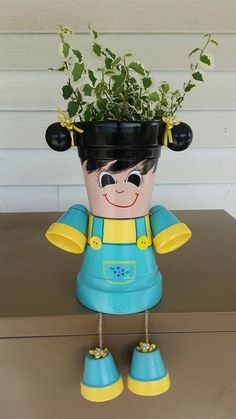 Little girl with pig tails /blue and yellow dress, planter pot person