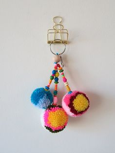 Flower Pom Pom Keychain made by Hye Jin Chung. This cute colorful pom pom keychain can brighten up your bag!   -This pom pom has a 1.6 round keychain and a mini silver metal swivel lobster clasp. -This pom pom is handmade with acrylic yarn and the strings are decorated with colorful wood beads. -Size: Approx 9L. -CARE AND USE- Dont pull pom poms.  *Due to the handmade nature of the product, the product might has some irregularities in finishing. *Colors may vary due to monitor settings…