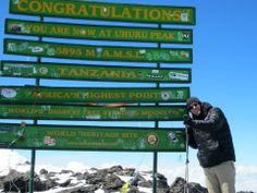 One of tourists at Kilimanjaro summit, climbing kilimanjaro through machame route is recommended and is success.  Kilimanjaro Tanzanite Safaris Co.Ltd offers kilimanjaro trekking expeditions, all tours are guided.