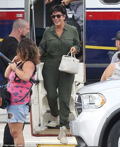 Coordinating: Kris also sported a long-sleeved olive green jumpsuit as she arrived on Monday, which she coupled with a pair of beige boots and a stylish beige handbag