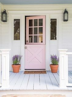 Giving your home curb appeal doesn't necessarily mean going all-out. Here, a painted door flanked by lanterns and terracotta pots creates a light, lovely, and inviting look.
